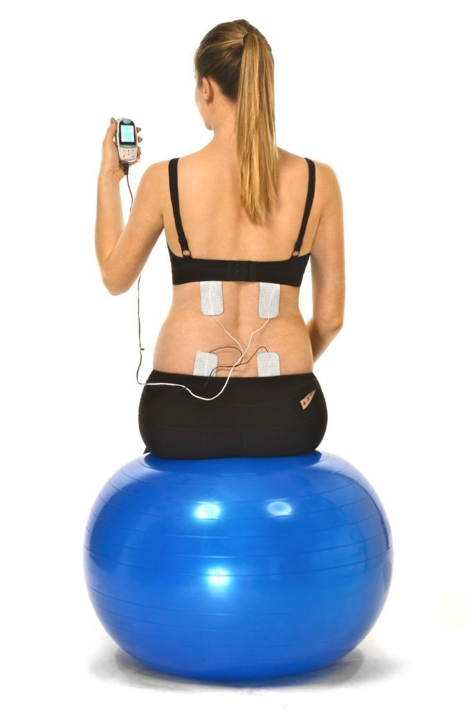 women on exercise ball with TENS pads on back